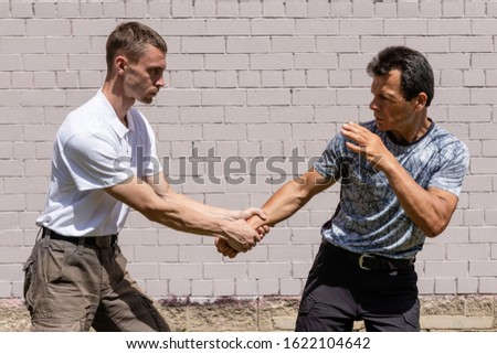 Martial arts instructors demonstrate self-defense techniques of Krav Maga. The attacker is trying to hold the man by the wrist. Opponents are ready for a fight.