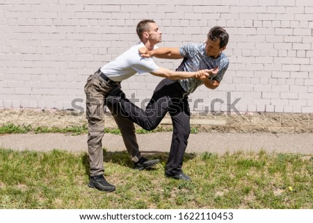 Martial arts instructors demonstrate self-defense techniques of Krav Maga. The defender performs a counter kick against the attacker, while fixing the hands of the attacker.