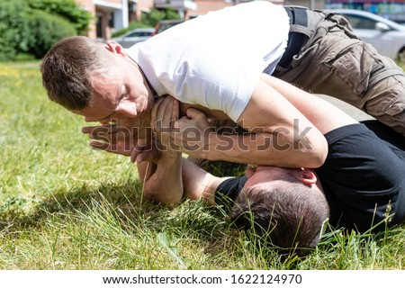 Martial arts instructors demonstrate self-defense techniques of Krav Maga. The opponent uses the technique to immobilize the attacker. Close-up.