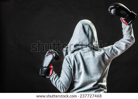 Martial arts or self defence concept. Sport boxer woman in gloves. Fitness girl training kick boxing back view on black background
