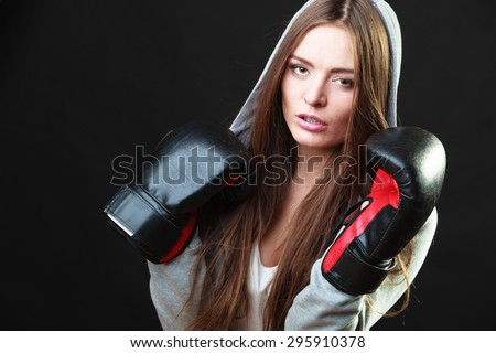 Martial arts or self defence concept. Sport boxer woman in gloves. Fitness girl training kick boxing on black background