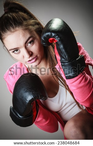 Martial arts or self defense concept. Sport boxer woman in black gloves. Fitness girl training kick boxing.