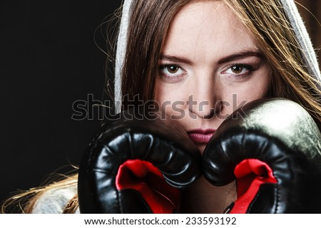 Martial arts or self defense concept. Sport boxer woman in gloves. Fitness girl training kick boxing on black background