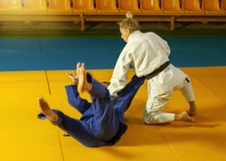 Martial arts. Sparing Portners. Sport man and woman in white and blue kimono train judo throws and captures in the sports hall