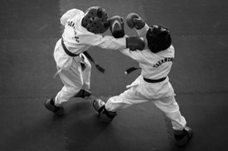 Martial Arts - Taekwondo. Kids in traditional kimano, hard hats and gloves. Sports duel. Black and white. For atmospheric added film noise effect. Text: Taekwondo is the name for martial art.