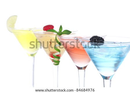 Martini alcohol cocktails in row blue hawaiian, tequila sunrise, garnished with cherry, lime, mint in martinis cocktail glasses on a white background. Focus on cocktail with blackberry