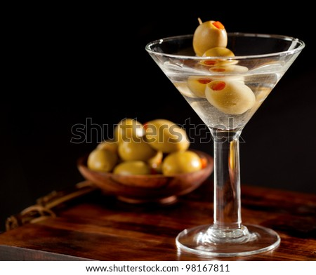 Martini and olives sitting on a wooden tray with black background