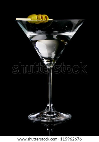 Martini glass and olives on grey background