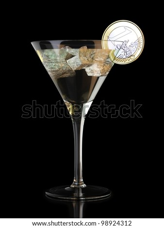 martini glass and sliced coin on black background