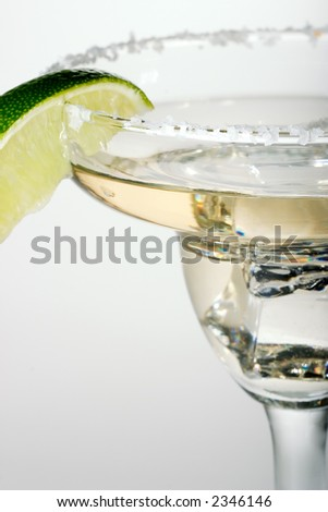 Martini glass full of cocktail with ice over white paper background served with lime