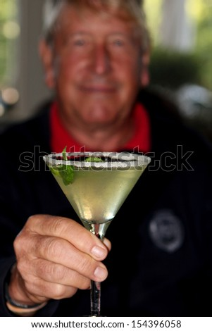 Martini glass held by senior male
