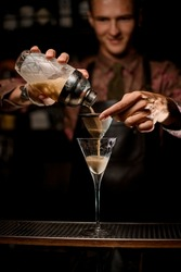 martini glass on bar and male hand holding sieve over it and gently pour liquid from glassy shaker. Blurry bartender in the background