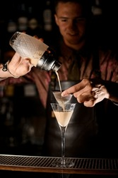 martini glass on bar and male hand holding sieve over it and pour liquid from glassy shaker. Blurry bartender in the background