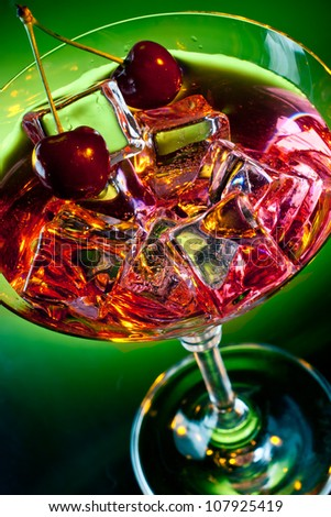 Martini glass with ice cubes and red drink with cherries