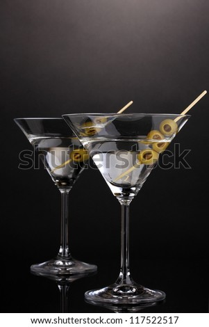 Martini glasses and olives on grey background