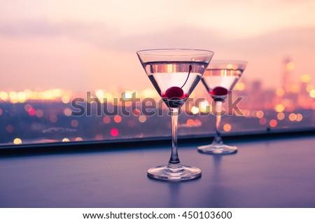 Martini glasses on a bar. City night life concept.