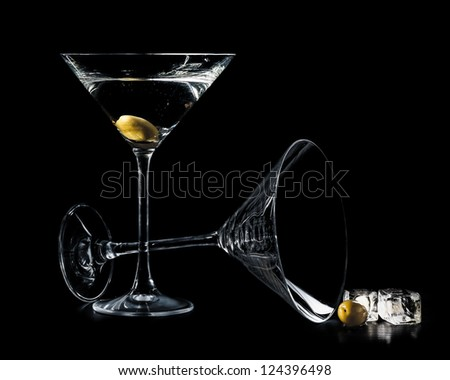 Martini in a cocktail glasses with olives and ice isolated on bl