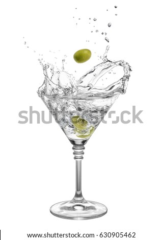 martini in glass with splashes isolated on white background. Green olive is falling in the alcohol cocktail