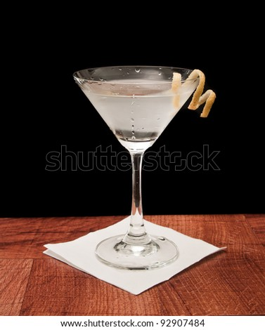 Martini on a bar garnished with a lemon twist isolated on a black background