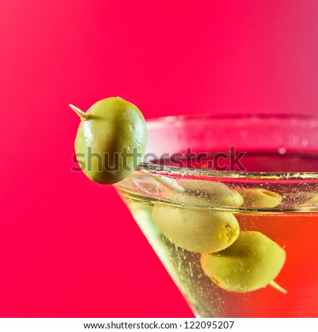 martini with green olives , focus on a foreground