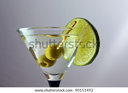 martini with lime and green olives on a grey background.