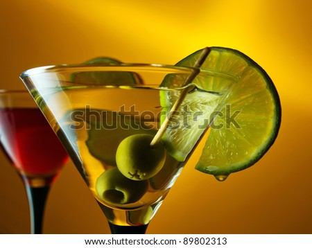 martini with lime and green olives on a orange background.