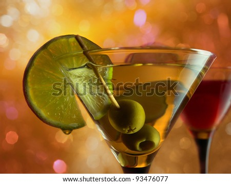 martini with lime and green olives on a orange background. - stock photo