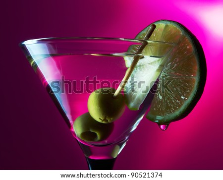 martini with lime and green olives on a purple background.