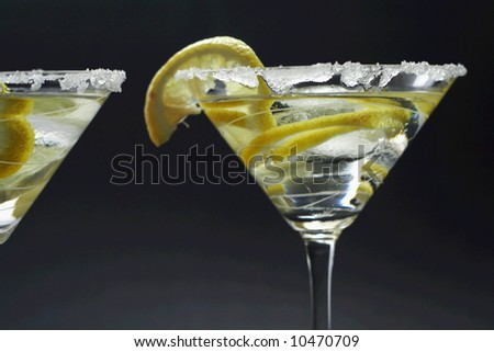 Martinis with sugar crust, lemon and peels - stock photo