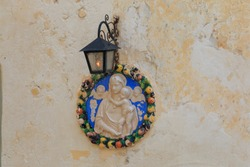 Mary and angels round bas-relief on soft limestone wall, Mdina, Valletta