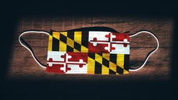 Maryland Flag. Coronavirus Covid 19 in U.S. State. Medical mask isolate on a black background. Face and mouth masks for protection against airborne infections in USA, America