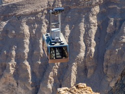 Masada/Israel - January 05 2020: Cable car ascending to Masada fortress. Masada is an ancient fortification on top of an isolated rock plateau overlooking the Dead Sea.