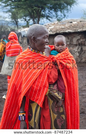MASAI MARA, KENYA - DECEMBER 28: An unidentified African woman with her baby pose for photos on December 28, 2009 in Masai Mara, Kenya. The Masai are a Nilotic ethnic group of semi-nomadic people located in Kenya and Tanzania.