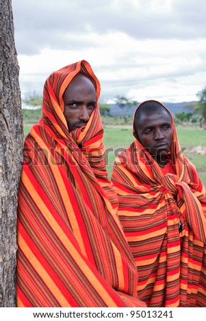MASAI MARA, KENYA - DECEMBER 28: Two unidentified African men pose for a portrait on December 28, 2009 in Masai Mara, Kenya. Masai are a Nilotic ethnic group of people located in Kenya and Tanzania.