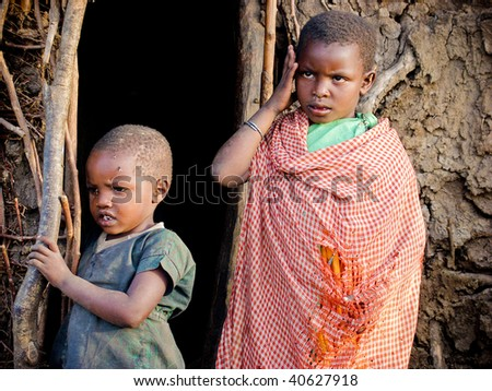 MASAI MARA, KENYA  - JANUARY 6: Small children standing in the door of the Masai tribe village house on January 6, 2004 in Masai Mara, Kenya. Social issue of poor African countries.