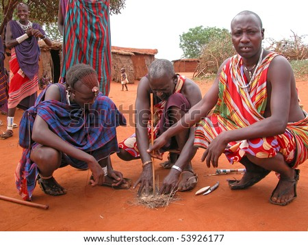MASAI VILLAGE - DECEMBER 01: Masai men making fire in a traditional way - village near the Tsavo East National Park - December 01, 2007 in Kenya.