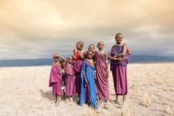Masai woman and a children in the African savannah, looking at camera.Tanzania