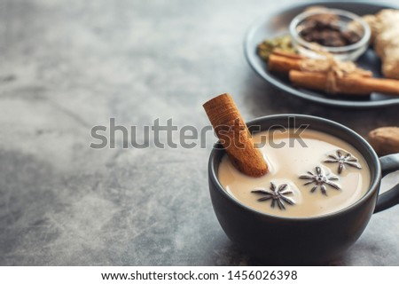 Masala tea. Traditional indian chai in black cup with spiced on grey background. With copy space. With copy space.