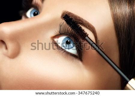 Mascara applying closeup, long lashes. Mascara brush. Eyelashes extensions. Make-up for blue eyes. Eye make up apply