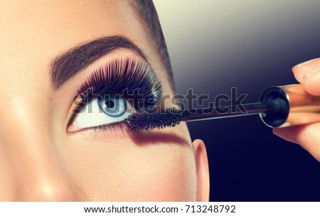 Mascara Applying. Long Lashes closeup. Mascara Brush. Eyelashes extensions. Makeup for Blue Eyes. Eye Make up Apply, Eyebrows shaping. Beautiful woman eyes make-up