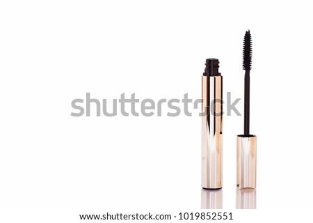 Mascara Bottle and Brush. Fashionable cosmetics Makeup for Eyes, Black Mascara wand and Tube Isolated on White. Extensible mascara and volume, Gold Bottle. Mascara on Light Background, New Form
