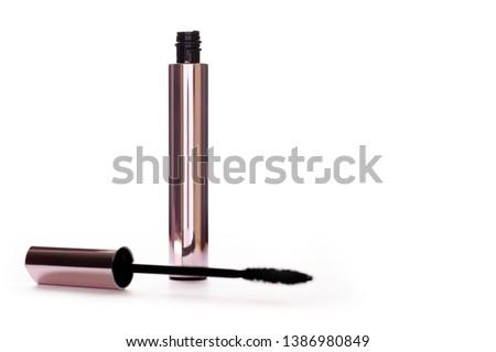 Mascara Bottle and Brush.Fashionable Makeup for the Eyes, Black Mascara wand and Tube Isolated on White.Gold Bottle.Mascara on  Light Background, New Form Brush.Mascara New Formula