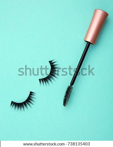 Mascara wand and false eyelashes on color background