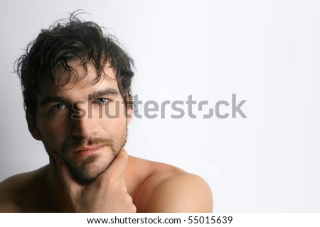 Masculine attractive young shirtless man with beard against white background