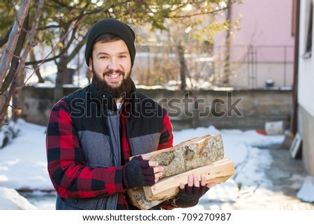 Masculine man carrying firewood for heat in the winter