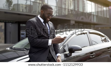 Masculine man in expensive suit waiting for companion, scrolling news on gadget #1112129933