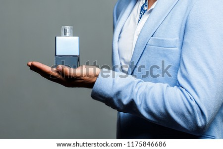 Masculine perfume, bearded man in a suit. Man perfume, fragrance. Male holding up bottle of perfume. Perfume or cologne bottle and perfumery, cosmetics, scent cologne bottle, male holding cologne.