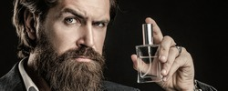 Masculine perfumery, bearded man in a suit. Male holding up bottle of perfume. Man perfume, fragrance. Perfume or cologne bottle, perfumery, cosmetics, scent cologne bottle, male holding cologne.