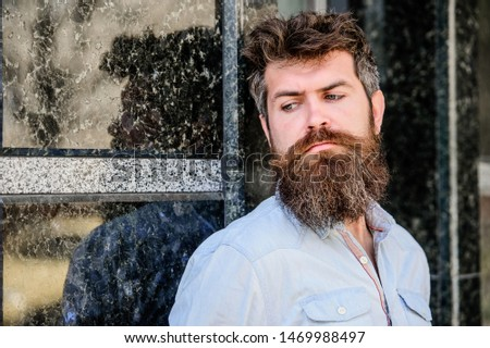 Masculinity and manliness. Confident posture of handsome man. Guy masculine appearance with long beard. Barber concept. Beard grooming. Beard care. Man attractive bearded hipster posing outdoors.
