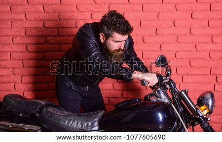 Masculinity concept. Hipster, brutal biker on serious face in leather jacket looks into mirror of motorcycle. Man with beard, biker in leather jacket near motor bike in garage, brick wall background.